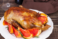 Festive Christmas duck baked with grapefruits and rosemary, glass of wine and candles. Royalty Free Stock Images