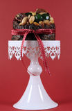 Festive Christmas food, fruit cake with glace cherries and nuts on white cake against a red background. Selective focus Royalty Free Stock Images