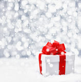 Festive Christmas gift in snow. Festive Christmas gift with a large ornamental red ribbon and bow in falling snow with a bokeh and copyspace Stock Photography