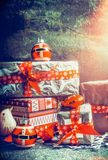 Festive Christmas gifts and presents decorating with handmade cut paper snowflakes and red ribbons on dark rustic background Stock Images