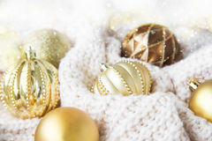 Festive Christmas golden globes with sparkle in woolen blanket. Festive Christmas golden globes with lights and sparkle on white fluffy woolen blanket Stock Photography