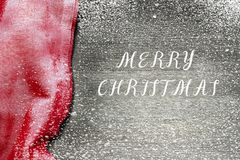 Festive Christmas holiday winter background with bright red tablecloth covered sparkling snowflakes on rustic wooden table. Frost pattern. Inscription Merry royalty free stock images