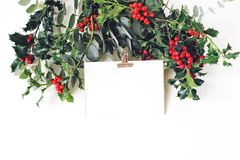 Festive Christmas mockup scene. Greeting card with golden paper binder clip, eucalyptus and holly red berries, leaves. And branches on white table background stock photography