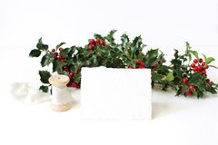 Festive Christmas mockup scene with handmade paper place card, spool of silk ribbon and holly red berries, leaves and. Branches on white table background stock image