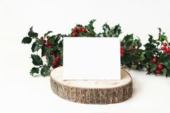Festive Christmas mockup scene with handmade paper place card on wooden cut board and holly red berries, leaves and. Branches. White table background, winter stock photos