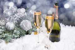 Festive Christmas and New Year champagne backdrop. Festive Christmas and New Year champagne background with two glasses and a bottle of champagne in winter snow Royalty Free Stock Images