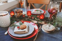 Festive Christmas and New Year table setting in red and grey tones. Dining place for celebration with handmade rustic details Stock Photo