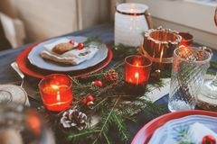Festive Christmas and New Year table setting in red and grey tones. Dining place for celebration with handmade rustic details Royalty Free Stock Image