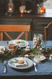 Festive Christmas and New Year table setting in scandinavian style with rustic handmade details in natural and white tones. Dining place decorated with pine Stock Images