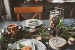 Festive Christmas and New Year table setting in scandinavian style with rustic handmade details in natural and white tones Royalty Free Stock Images