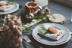Festive Christmas and New Year table setting in scandinavian style with rustic handmade details in natural and white tones. Dining place decorated with pine Royalty Free Stock Image