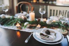 Festive Christmas and New Year table setting in scandinavian style with rustic handmade details in natural and white tones Stock Photography