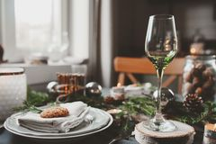 Festive Christmas and New Year table setting in scandinavian style with rustic handmade details in natural and white tones Royalty Free Stock Photography
