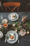 Festive Christmas and New Year table setting in scandinavian style with rustic handmade details in natural and white tones Royalty Free Stock Image