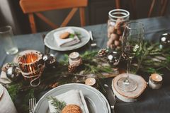Festive Christmas and New Year table setting in scandinavian style with rustic handmade details in natural and white tones Royalty Free Stock Photo