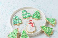 Festive Christmas snowman Cookie with decorated trees on white background. Royalty Free Stock Images