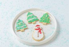 Festive Christmas snowman Cookie with decorated trees on white background. Royalty Free Stock Photos