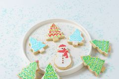 Festive Christmas snowman Cookie with decorated trees on white background. Stock Photos