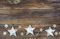 Festive Christmas Stars. Christmas background with festive stars decoration on wooden board Stock Photos