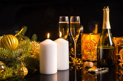 Festive Christmas still life with champagne. In a bottle and flutes, burning white candles and golden gifts and baubles over a dark background Stock Photos