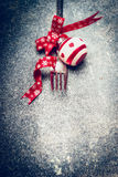 Festive Christmas table place setting with fork, red ribbon and ball on dark rustic vintage background Royalty Free Stock Photography