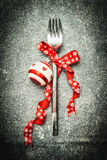 Festive Christmas table setting with fork, red ribbon and ball on dark rustic vintage background. Top view Royalty Free Stock Images