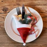 Festive Christmas table setting with a Santa Hat. Festive Christmas table setting with a red Santa Hat filled with a napkin, cutlery and decorations on a white Stock Photos