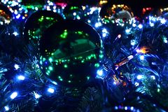 Festive Christmas tree decorated with large bright balls and a garland, bottom view of the ball closeup. stock photo