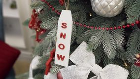 Festive christmas tree decorated with snow,silver bright ribbon ,pine cones and red garland. Slow motion of beautiful decorated chrismas tree with different stock footage