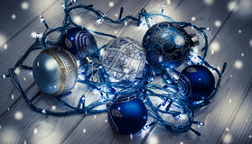 Festive Christmas tree decorations. Beautiful decor for the Christmas holidays. Radiant electric Christmas tree garland and blue glass Christmas balls. Merry Stock Images