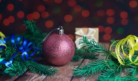 Festive christmas tree and gift box packing with serpentine. Festive christmas tree and gift box packing and toy ball  on a wooden beautiful background Royalty Free Stock Photo