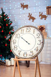 Festive Christmas vintage watches04. Vintage clock with an arrow in the room with the Christmas tree, space for text five minutes before midnight Royalty Free Stock Photo