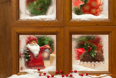 Festive Christmas Window. Festive Christmas frosty window with figgy pudding and father Xmas ornament, focus on Christmas pudding Royalty Free Stock Photos