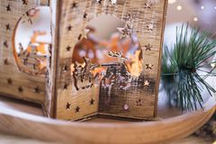 Festive Christmas wooden lantern closeup with fir tree and sparkle lights. Selective focus royalty free stock images