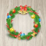 Festive Christmas wreath with balls, bells, mistletoe, tree cone and bow. Isolated on wooden background Stock Photo