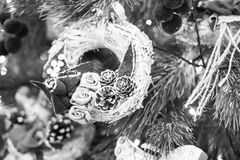 Festive christmas wreath. Beautiful traditional festive christmas tree decoration of pine cone and straw wreath for new year holiday hanging on green fir tree Royalty Free Stock Image