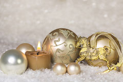Festive classical christmas decoration in white and gold with ho. Rse and one burning candle for the first advent Royalty Free Stock Images