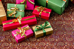 Festive Cloth, Half Covered with Gifts. Small presents placed on a festive cloth. All wrapped in gold, red, green and magenta. Plenty of text space. Rich Stock Images