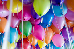 Festive, colorful balloons with helium attachment to the white ribbons Royalty Free Stock Photo