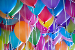 festive, colorful balloons with helium attachment to the white ribbons Stock Photography