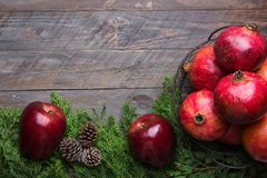 Festive colorful botanical Christmas composition. Fresh green juniper red apples pomegranates in wire basket pine cones on wood stock photos