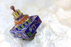 Festive colorful enameled Hanukkah dreidel on a soft white background Stock Photography
