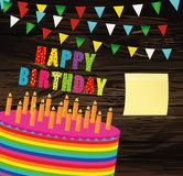 Festive colorful rainbow and a big cake with candles. Happy Birt. Hday. Empty Yellow sheet of paper for notes. Sticker. Greeting card or invitation for a holiday Royalty Free Stock Image