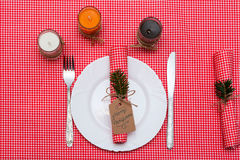 Festive composition with candles and plates. Table decoration. A beautiful table setting, red table cloth, tablecloth in the box. Stock Photo