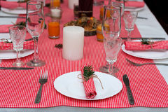 Festive composition with candles and plates. Table decoration. A beautiful table setting, red table cloth, tablecloth in the box. Royalty Free Stock Images