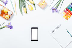 Festive composition: flowers, easter eggs, mobile phone and note Stock Photo