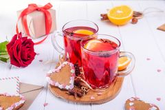 Festive composition with greeting card, cookies, flower, gift and hot drink with fruits or mulled wine on the white wooden table. Valentine` s day surprize for Royalty Free Stock Image