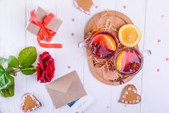 Festive composition with greeting card, cookies, flower, gift and hot drink with fruits or mulled wine on the white wooden table. Valentine` s day surprize for Stock Photo