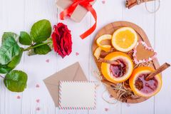 Festive composition with greeting card, fresh flower, gift and unusual served in orange mulled wine on the white wooden table. Val. Entine` s day surprize for Royalty Free Stock Photo