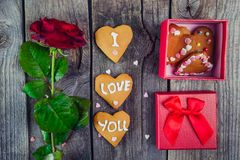 Festive composition with homemade cookies in shape of heart with I Love you lettering, fresh rose flower, gift box. Gift for lover. On Valentine`s day. Vintage Stock Photography